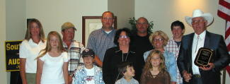 The family and friends of Vernell Qualm, Platte, join him as he is presented with a plaque in honor of